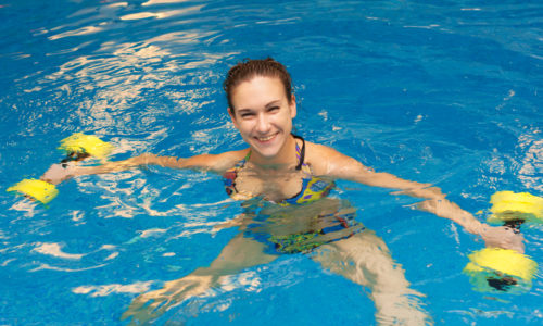 Woman smiling in aqua aerobics with dumbbells. Water aerobic