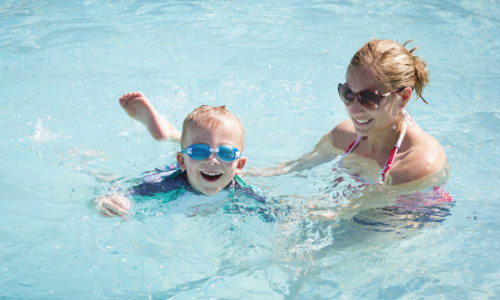 A women helps a happy young boy learn how to swim in a swimming pool